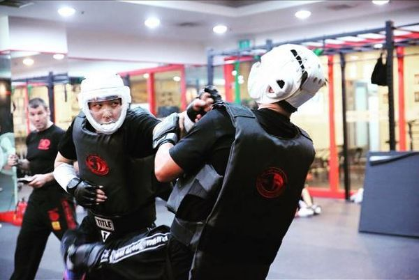 Krav Maga students doing sparring under the supervision of a Krav Maga instructor