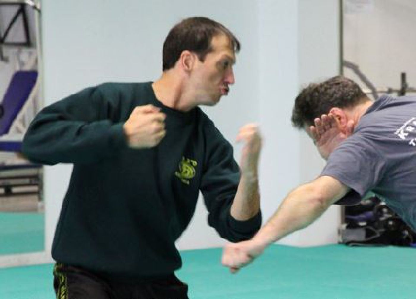 Krav Maga Instructor demonstrating how to deflect an attacker's punch to counter